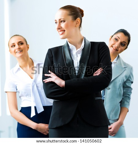 successful business woman in the office, colleagues stare over his shoulder - stock photo