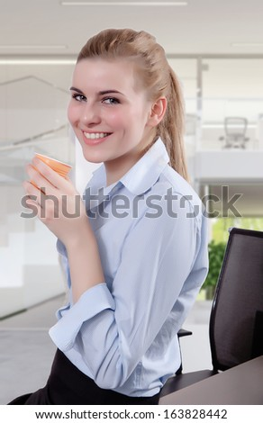 Successful business woman looking in the camera with a cup of coffee in her hand. Copy space.