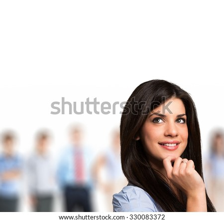 Successful business woman looking up with her staff in the background - stock photo