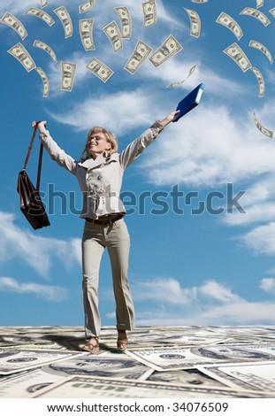 Successful business woman running in a dollar rain - stock photo