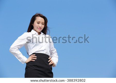Successful business woman smile to you with blue sky, asian beauty - stock photo