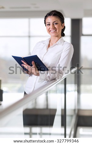 Successful business woman standing in an office building meeting room, holding planner - stock photo