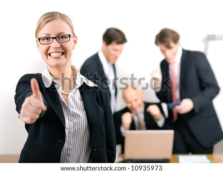 Successful business woman standing in front of her colleagues; selective focus on woman - stock photo