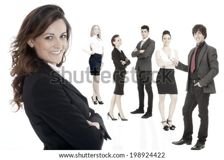 Successful business woman standing with her staff in background  - stock photo