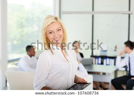 Successful business woman using tablet in office - stock photo