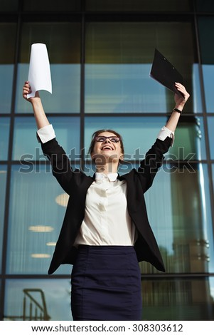 Successful business woman with arms up and documents. Happy young business woman made a deal. Business peolple concept
