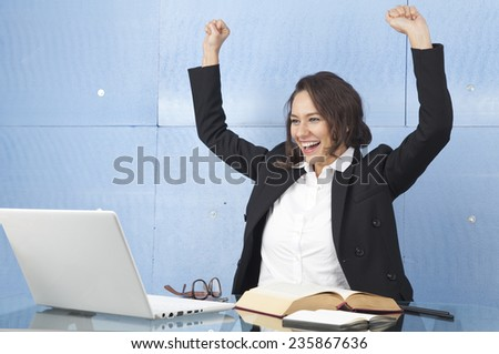 Successful business woman with arms up in the office - stock photo