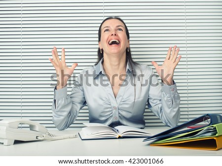 Successful business woman with arms up sitting at office desk - stock photo
