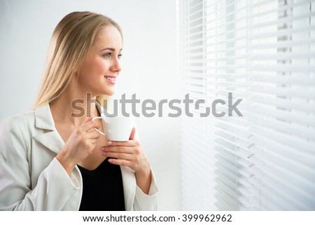 Successful business woman with cup of coffe at a window - stock photo