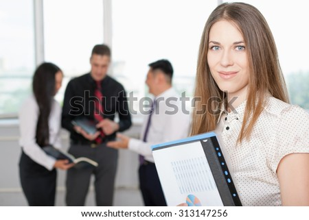 Successful business woman with documents folder at foreground and business team of men and woman at background. Image symbolizes a successful corporation or company