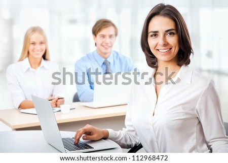 Successful business woman with her staff in background at office - stock photo