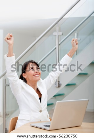 Successful business woman working on a laptop at the office and smiling - stock photo