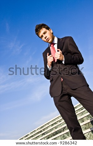 Successful businessman against blue sky background - stock photo