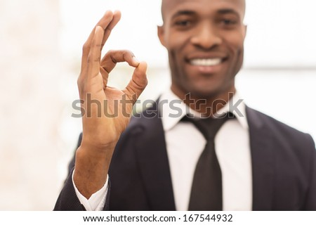 Successful businessman. Cheerful young African man in formalwear gesturing and smiling at camera - stock photo
