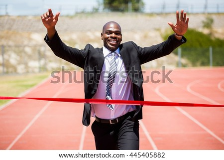 Successful businessman crossing the finishing line red ribbon