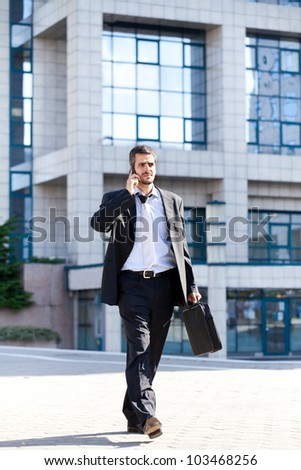 Successful businessman doing business on mobile phone, full length