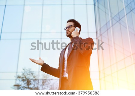 Successful businessman dressed in luxury suit talking on mobile smart phone while standing outside of skyscraper, young male banker discussing problems in work via cell telephone after doing reports - stock photo
