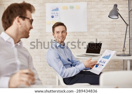 Successful businessman explaining charts to colleague in office - stock photo