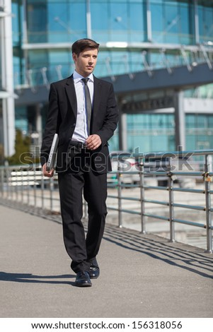 Successful businessman. Full length of cheerful young men in formalwear holding laptop while walking outdoors - stock photo
