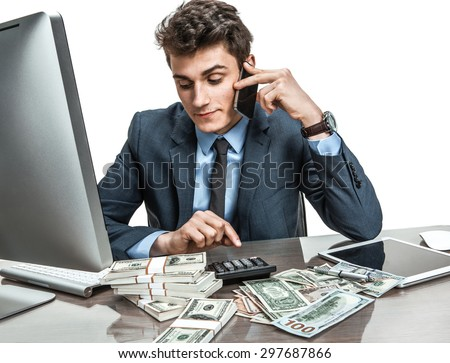 Successful businessman going to make a call by cell phone while working with PC computer and calculator - stock photo