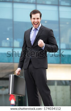 successful businessman happy after a good job in front of an office building  - stock photo