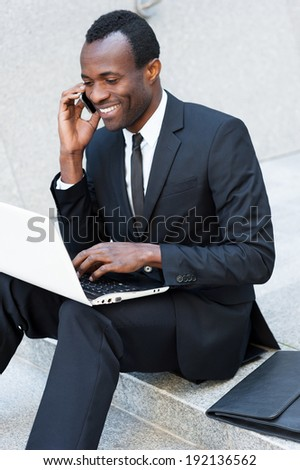 Successful businessman. Happy young African man in formal wear talking on the mobile phone and working on laptop while sitting on outdoors staircase