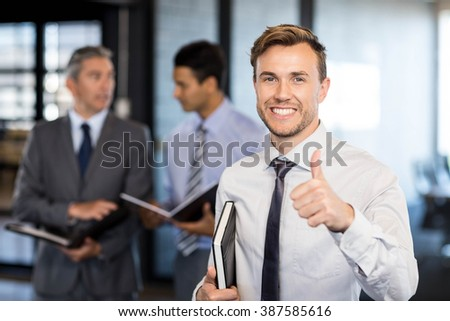Successful businessman holding his thumbs up while celebrating victory in office - stock photo