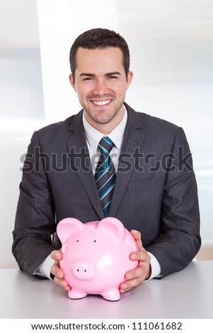 Successful businessman holding piggybank at the office