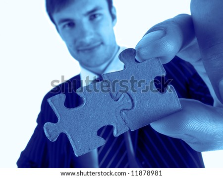 successful businessman in  hand holds red puzzle, close-up