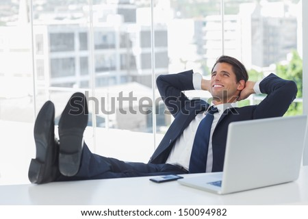 Successful businessman in his office relaxing with his feet on his desk - stock photo