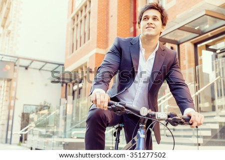 Successful businessman in suit with bicycle in city - stock photo
