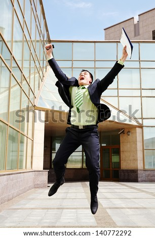 Successful businessman jumping near his office - stock photo