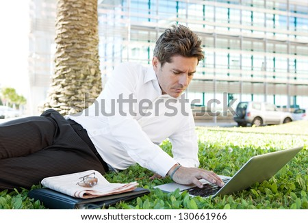 Successful businessman laying down on green grass near a modern glass office building in the financial city district, using a laptop computer. - stock photo