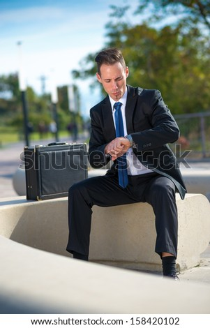 Successful businessman looking at his watches while sitting in the park - stock photo