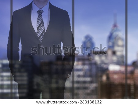 Successful businessman looking through the window on night city