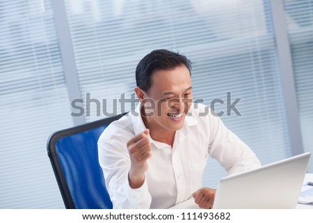 Successful businessman looking very happy sitting at the table with laptop - stock photo