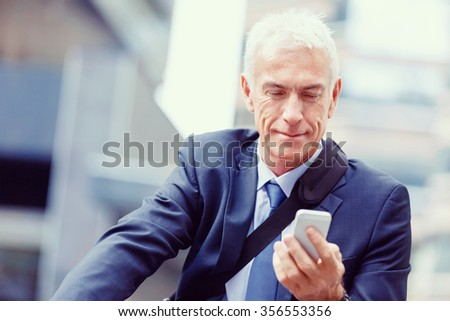 Successful businessman on bicycle in city holding mobile phone - stock photo