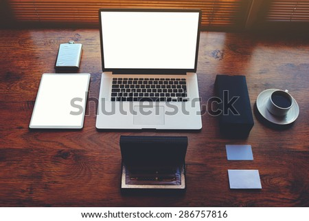 Successful businessman or entrepreneur table with style accessories, pen case, open laptop computer and digital tablet with white blank copy space screen for text information or content, e-business - stock photo