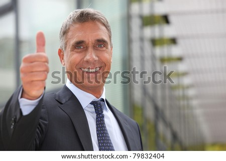 Successful businessman outside building - stock photo