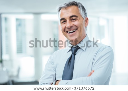 Successful businessman posing with crossed arms and smiling at camera - stock photo