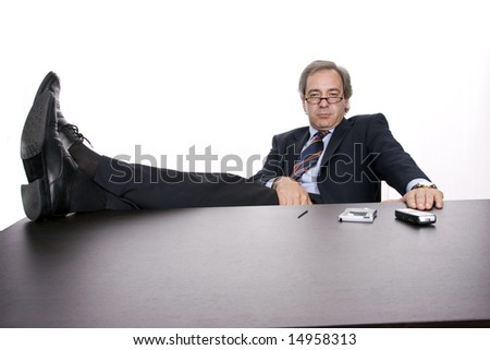 Successful businessman relaxing over his desk, isolated in white background