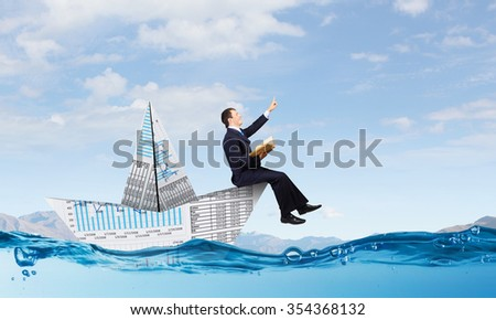 Successful businessman sailing on paper boat in financial sea