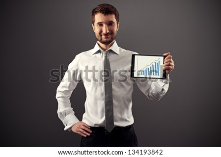 successful businessman showing growth chart and smiling - stock photo