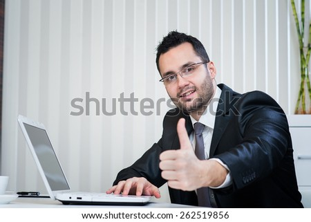 Successful businessman showing thumbs up at business office. - stock photo