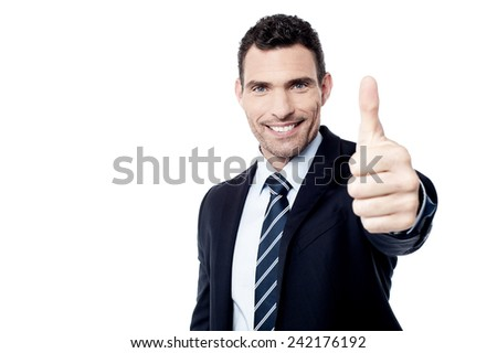 Successful businessman showing thumbs up gesture - stock photo