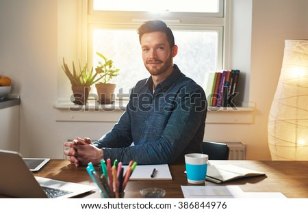 Successful businessman sitting at his desk in his home office thinking as he looks at the camera with a pensive expression - stock photo