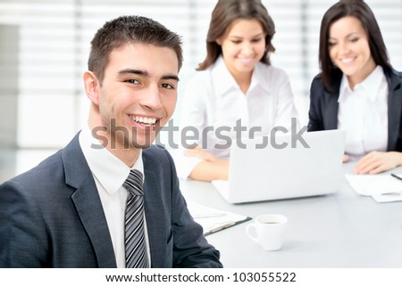 Successful businessman sitting with his team at office - stock photo