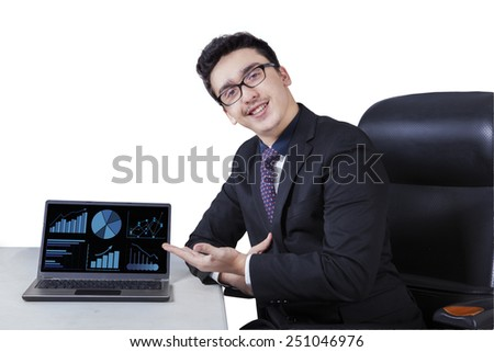 Successful businessman smiling happy at the camera while showing financial chart on laptop computer - stock photo