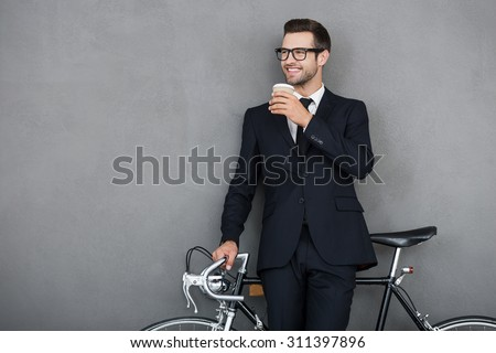 Successful businessman. Smiling young man leaning at his bicycle and holding cup of coffee while standing against grey background - stock photo