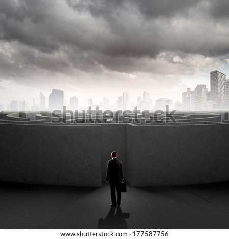 Successful businessman standing near the entrance of labyrinth - stock photo